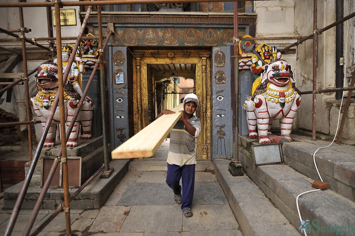बसन्तपुर परिसरमा पुनर्निर्माण भइरहको मठमन्दिरको लागि काठ ओसार्दै एक कालीगढ। तस्बिरः नारायण महर्जन
