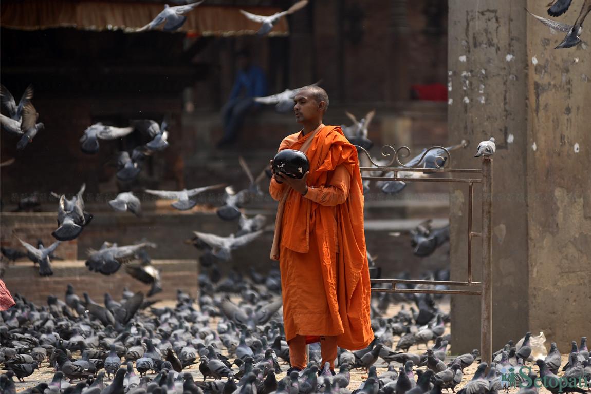बसन्तपुर दरवार परिसरमा भिक्षा माग्दै एक भिक्षु। तस्बिरः नारायण महर्जन