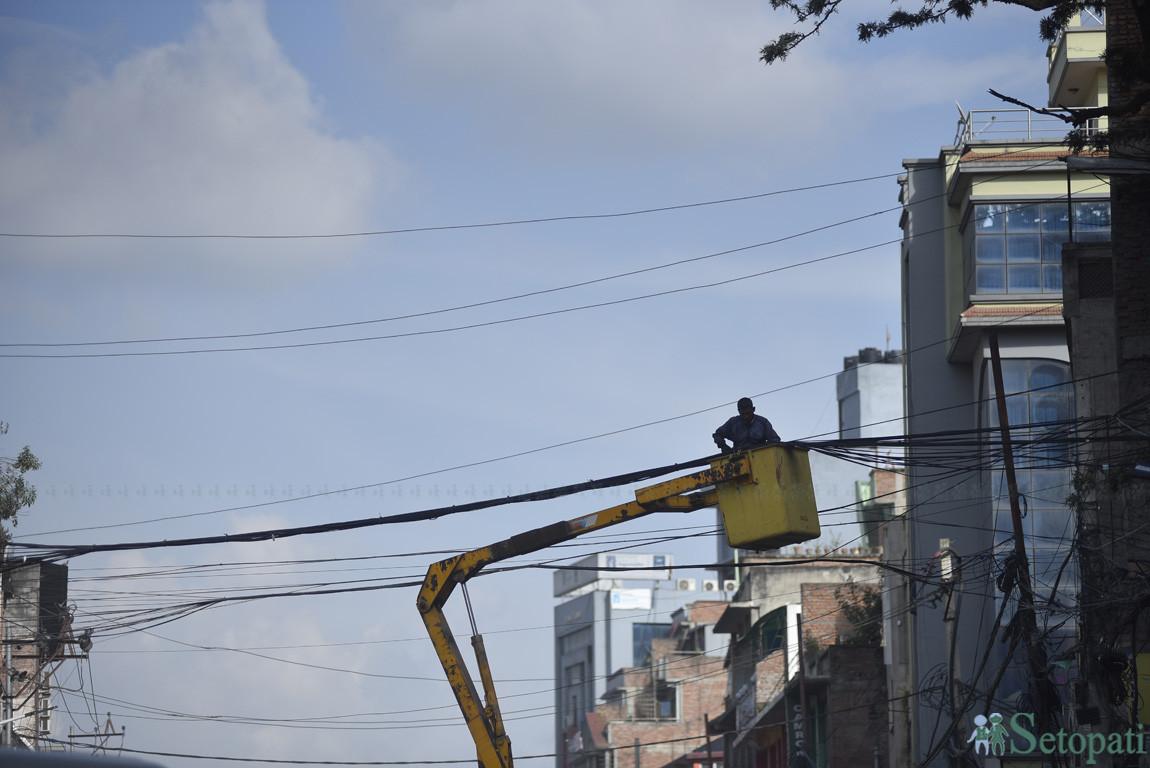 काठमाडौंको टेकुस्थित सडकमा असरल्ल छरिएका बिजुलीका तारहरू मिलाउँदै नेपाल विद्युत प्राधिकरणका कर्मचारी। तस्बिरः नारायण महर्जन
