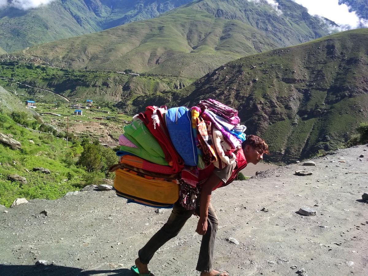 खासाबाट ल्याइएको कपडा बेच्नका लागि गाँउमा लैजाँदै कालीकोटका व्यापारी । प्रत्येक बर्ष डोल्पामा व्यापारीले बोकेर लाखौँको कपडा बिक्री गर्छन । तस्बिर: रासस