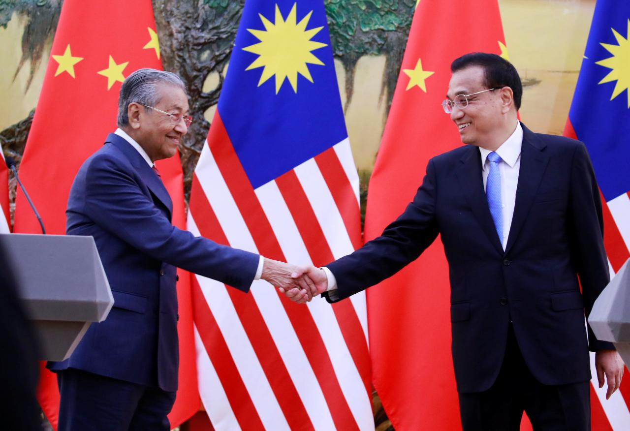 चीन भ्रमणमा रहेका मलेसियाली प्रधानमन्त्री महाथिर समकक्षी ली खछ्याङसँग हात मिलाउँदै।