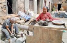 भक्तपुरको मध्यपुरथिमि–५ नासःननीचोकका सिद्धिबहादुर प्रजापति र उनीकी पत्नी मिश्री प्रजापति माटोको भाडा बनाउनका लागि माटो तयार पार्दै । तस्वीर : रासस